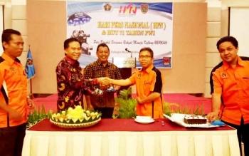 Ketua DPRD Kapuas, Algrin Gasan menerima potongan kue ulang tahun PWI ke 71 dari Ketua PWI Provinsi Kalteng Sutransyah.