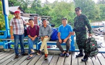 Pasi Intel Kodim 1016/Plk Kapten Inf Suradi (kanan) anggota Imigrasi Palangka Raya (kiri) menunjukan tiga dari empat WNA China yang ditangkap, Selasa (21/2/2017).
