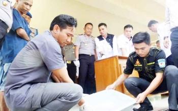 Dua orang anggota sedang membuang cairan pelarut barang bukti sabu yang disaksikan langsung oleh pemiliknya dan juga Bupati Kotim Supian Hadi bersama Kapolres Kotim AKBP Hendra Wirawan, Rabu (22/2/2017).