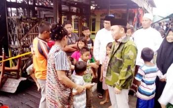 Gubernur Kalteng Sugianto Sabran dikelilingi beberapa anak usia sekolah saat menengo korban kebakaran di Gang Mandau