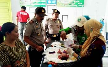 Kapolsek Baamang Iptu I Made Rudia mengecek langsung kondisi bayi yang ditemukan warga, Kamis (23/2/2017).