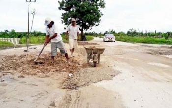 Warga Desa Natai Raya bergotong royong memperbaiki jalan Pangkalan Lima-Kumai.