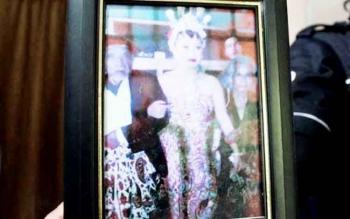 Sebuah pigura berisi foto Ibu Linda atau Cempaka Aji Jaka Slewah, berdandan khas pengantin perempuan Jawa sedang menggandeng Mbah Gini (kiri) dan seorang wanita lanjut usia.