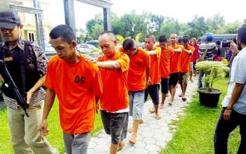 Tersangka pengedar narkoba digiring anggota Direktorat Reserse Narkoba Polda Kalteng menuju ruang tahanan, Jumat (24/2/2017).
