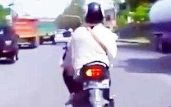 Seorang perempuan berkendara sambil menyalakan lampu isyarat belok.