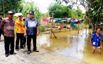 Ketua DPRD Kabupaten Gunung Mas Gumer (kiri) bersama Wakil Ketua DPRD Punding S Merang dan perwakilan Dinas Sosial serta Lurah Tampang Tumbang Anjir meninjau lokasi banjir, Jumat (24/2/2017).