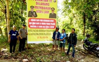 Anggota Polsek Dusun Utara, Kabupaten Barito Selatan, memasang spanduk larangan membakar hutan dan lahan.