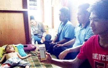 Lukman (kanan), ayah kandung Lutfhi menunjukan vitamin yang diberikan dokter RSSI untuk penyembuhan Luthfi di kediamannya jalan Rambutan Kelurahan Baru Pangkalan Bun, Jumat (24/2/2017).