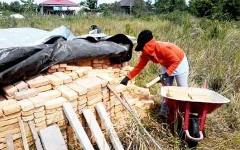 Seorang warga Kasongan bersiap mengangkut batu bata merah dari tumpukan menggunakan arko untuk membangun rumah.
