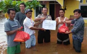 Camat Cempaga Hulu Ubaidillah dan Kapolsek Iptu AA Rahmat menyerahkan bantuan kepada korban banjir.