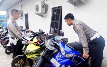 Dua anggota Satlantas Polres Kotim tengah memeriksa sepeda motor yang terjaring karena digunakan untuk aksi balapan liar.