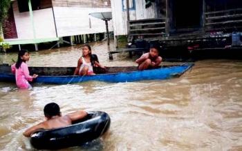 Anak-anak di desa Nangamoa Kecamatan Arut Utara Kabupaten Kobar menggunakan perahu dan karet ban di atas genangan banjir yang merendam sekurangnya 60 rumah di dua RT di desa tersebut, Senin (27/2/2017).