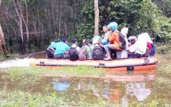 Petugas BPBD Murung Raya mengerahkan perahu karet untuk menyeberangan para pelajar di Juking Pajang menuju Kota Puruk Cahu karena akses masuk desa tersebut masih tergenang banjir, Selasa (28/2) pagi.