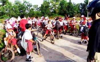 Puluhan murid SDN I Baamang Barat berdiri di luar karena tidak bisa masuk ke areal sekolah akibat pagar dikunci oleh pihak sekolah.