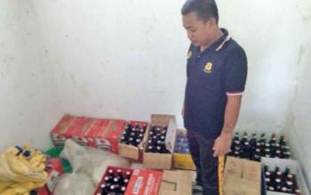 Anggota Satpol PP menunjukkan puluhan botol miras yang diamankan saat razia pekat, Senin (27/2/2017) malam.