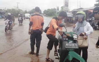 Sejumlah petugas DPBD Kotim membantu seorang pengendara yang motornya mogok setelah menerobos banjir di Jalan Jenderal Sudirman km 4, arah Sampit-Pangkalan Bun.