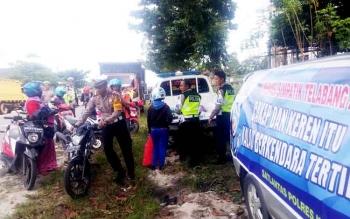 Kasat Lantas Polres Kobar, AKP Asdini Pratama Putra (dua kiri) mendorong sepeda motor milik pengendara yang tidak dilengkapi kaca spion dalam operasi Simpatik Telabang, Rabu (1/3/2017).