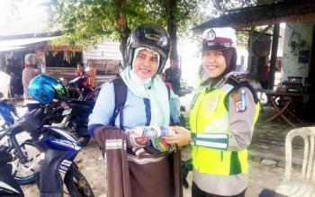 Salawati (kiri) mendapat hadiah dari salah satu Polwan yang bertugas di Satlantas Polres Kobar saat operasi Simpatik Telabang di jalan Pasir Panjang dekat Bundaran Monyet, Kecamatan Kumai, Rabu (1/3/2017).