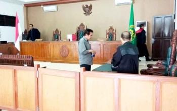 Mantan Rektor Universitas Palangka Raya Henry Singarasa berdiskusi dengan penasehat hukumnya seusai menjalani sidang, Rabu (1/3/2017)