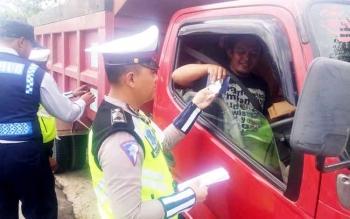 Anggota Satlantas Polres Kobar memeriksa surat-surat kendaraan sopir truk saat Operasi Simpatik Telabang di di Bundaran Monyet, Kumai, Kotawaringin Barat, Rabu (1/3/2017).