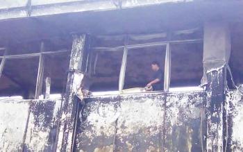 Petugas kepolisian memasang garis polisi di titik yang diduga asal api dalam peristiwa kebakaran kantor Gubernur Kalteng pad 1 November 2015.