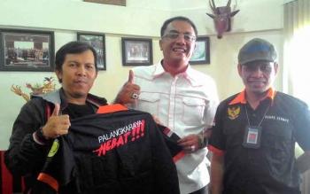 Ketua DPRD Kota Palangka Raya Sigit K Yunianto (tengah) menunjukkan baju seragam yang diberikan kepada awak media yang bertugas di DPRD Kota Palangka Raya.