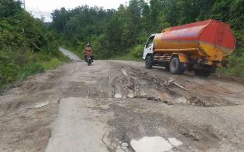 Sebuah truk melintasi jalan yang rusak parah di ruas Kuala Kurun-Palangka Raya, Kamis (2/3/2017).