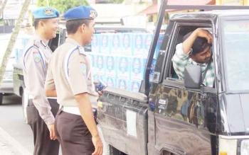 Tampak sejumlah anggota tetap tersenyum saat mengingatkan pengendara untuk menggunakan sabuk pengaman saat mengemudi.
