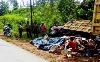 Sejumlah warga dan polisi membantu evakuasi muatan truk terguling, Kamis (2/3/2017).
