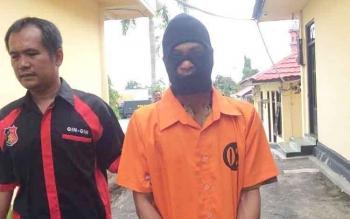 Tersangka Lambri (kanan) memakai penutup wajah saat digiring polisi di Mapolres Kobar usai gelar perkara baru baru ini.