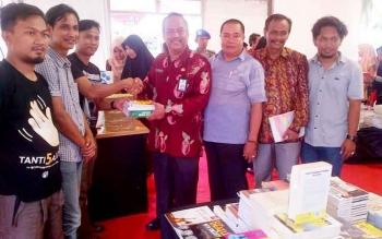 Penyelanggaran book fair menyerahkan buku kepada Kepala Dinas Perpustakaan dan Kearsipan Kabupaten Barito Selatan Agus Taruna, Jumat (3/3/2017).