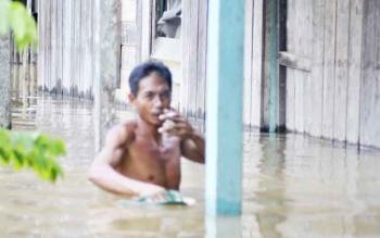 Warga berjalan di tengah banjir yang menerpa rumahnya di Desa Sukarami, Kecamatan Arut Utara.