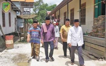 Bupati Barito Utara Nadalsyah saat jalan bersama warga desa Sabuh setelah melakukan peninjauan jalan.
