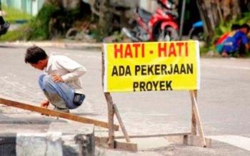 Salah satu pekerja dari pihak rekanan sedang melakukan perbaikan jalan di Pangkalan Bun, baru-baru ini. Dinas PUPR menganggarkan Rp1,5 miliar untuk program unit pemeliharaan rutin (UPR) jalan.