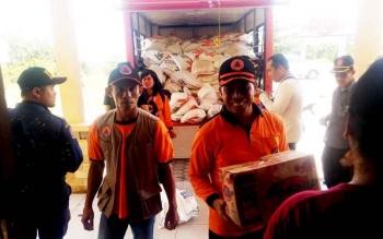 Kepala BPBD Kobar, Hermon F Lion (kanan) tengah menurunkan bantuan berupa mie instan untuk bantuan korban banjir Aruta, di Kantor Kecamatan Aruta, Minggu (5/3/2017).
