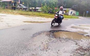 Pengendara sepeda motor melewati titik yang rusak di Jalan Damang Gaman, Kuala Kurun, Kabupaten Gunung Mas (Gumas), Minggu (5/3/2017)