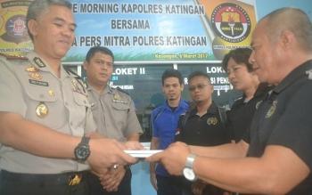 Ketua PWI Kabupaten Katingan Aris Munandar memberikan cindera mata berupa buku putih PWI kepada Kapolres Katingan AKBP Tato P Suyono saat acara coffee morning, Senin (6/3/2017)