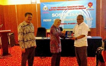 Wakil Ketua Kadin Kalteng Anthon Pawarangan (kanan) menerima cinderamata dari Komisioner KPPU Saidah Sakwan didampingi Komisioner KPPU Kamser Lumbanradja (kiri), Senin (6/3/2017).