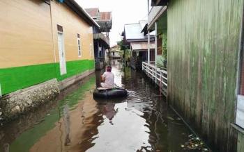 warga Gang Peraguai, Barito Utara menggunakan ban karet untuk beraktivitas karena jalan terendam air hingga satu meter lebih. Jalan Merak, Muara Teweh sudah terendam air hingga setengah meter, menyebabkan jalur utama kota ini terganggu