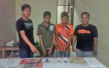 Gustino, warga Buntut Bali, Kecamatan Pulau Malan dan Suprianto, warga Pendahara, Kecamatan Tewang Sanggalang Garing (tengah), ditangkap polisi karena bermain judi bola gulir.