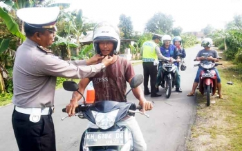 Kanit Lantas Polres Barsel, mengklik helm pengendara saat razia Operasi Telabang, Selasa (7/3/2017)