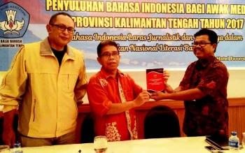 Kepala Balai Bahasa Kalteng Haruddin (kanan) menyerahkan buku UU RI Nomor 24 tahun 2009 tentang Bendera, Bahasa, Lambang Negara dan Lagu Kebangsaan kepada Sutransyah, Ketua PWI Kalteng didampingi Tendy K Somantri yang menjadi salah satu narasumber.