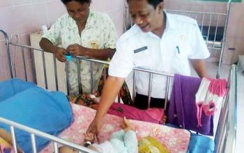Mutiara (kiri) ibu dari Fely (11) bulan yang terkena penyakit gizi buruk menyaksikan kedatangan Direktur RSUD Mas Amsyar Noor Sanuri yang melihat kondisi buah hatinya, Rabu (8/3/2017).