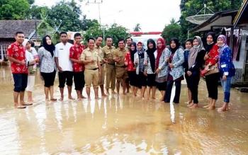 Tim medis gabungan di sela pengobatan di salah satu desa yang terkena banjir.