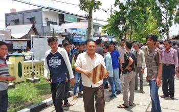 Wakil Ketua I DPRD Barsel, Hasanuddin Agani memegang stop map batik