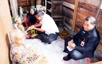 Penjabat Sekda Kalteng Sahrin Daulay saat menyerahkan bantuan gubernur kepada nenek Aminah saat menyambangi gubuk tua di Jalan Pelatuk, Rabu (8/3/2017)