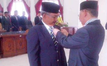 Wakil ketua DPRD Barsel, Hasanuddin Agani (kanan) memasangkan pin kepada Akhmad Fauzi sebagai tanda yang bersangkutan resmi menjadi anggota DPRD Barsel.