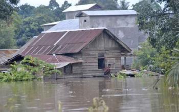 Warga Kelurahan Pangkut, Kecamatan Arut Utara, Kotawaringin Barat, berada di luar rumah yang terendam banjir. Saat ini, Kamis (9/3/2017), air mulai surut.