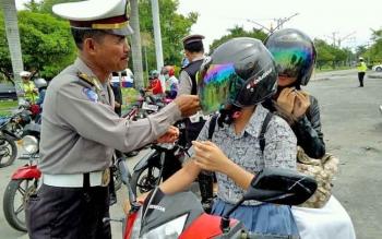 Anggota Ditlantas Polda Kalteng menegur pelajar yang tidak mengklik helm saat berkendara.