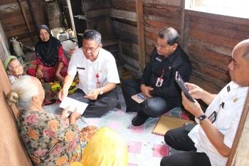 Plt Sekda Kalteng Sahrin Daulay menyerahkan amplop berisi uang kepada nenek Aminah